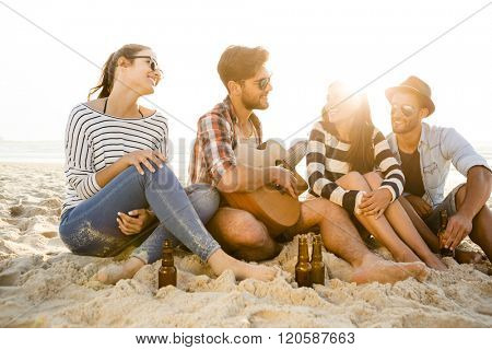 Friends having fun together at the beach, playing guitar and drinking beer