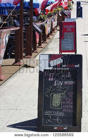 SAINT JOHN, NEW BUNSWICK, CANADA - JUNE 27, 2014: Sign in front of the restaurant advertising happy hour deal on Canada Day in Saint John in New Brunswick