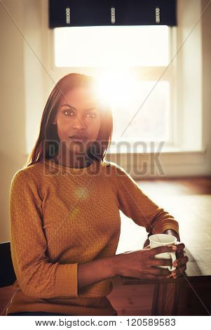 Serious Black Woman At Table In Front Of Window
