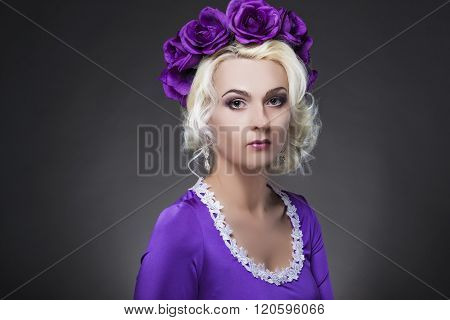 Fashion And Beauty Concepts.portrait Of Caucasian Blond Female Model In Purple Dress With Violet Flo