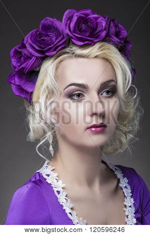 Beauty Concepts. Closeup Portrait Of Caucasian Blond Female Model In Purple Dress With Violet Flower