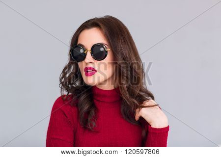 Attractive woman in glasses standing on grey background