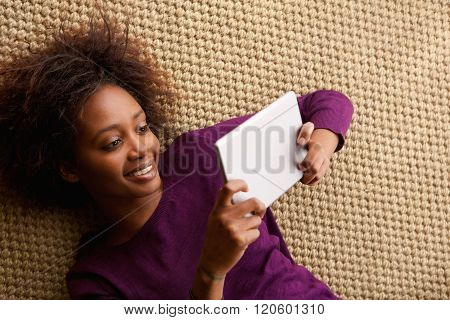 Smiling Woman Lying Down With Digital Tablet