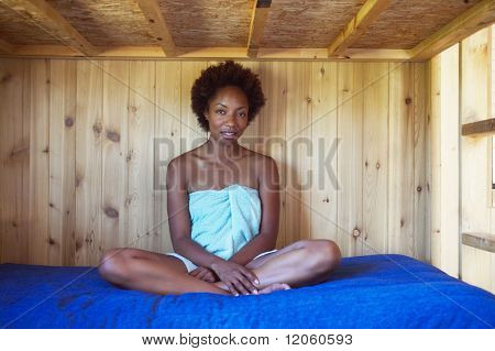 African American woman in towel sitting on wooden bunk