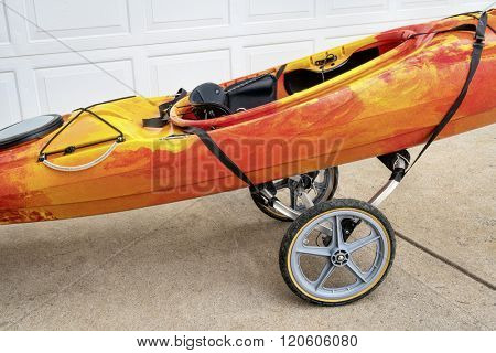 colorful river kayak on a folding cart in a driveway - river running shuttle concept