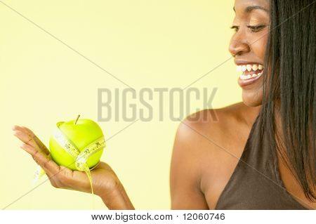 Woman holding apple and tape measure