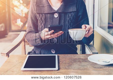 Woman Using Smartphone In Coffee Shop And Soft Light With Vintage Filter.
