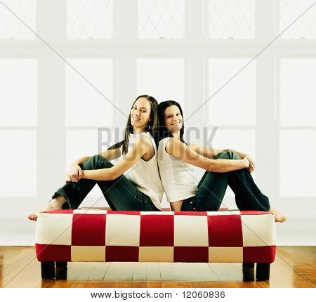 Two young women sitting back to back