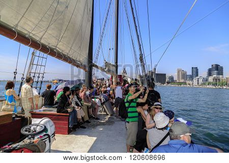 People travel on old vintage tall ship toward downtown Toronto