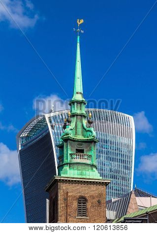 LONDON, UK -JUNE 6, 2015: Small church on Trinity Square on London City with Walkie-Talkie' building and blue sky background. England