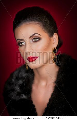Attractive sexy young woman wearing a fur coat posing in studio on dark purple background