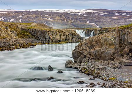 The Skjalfandafljot river in Iceland with the Godafoss waterfall in the back