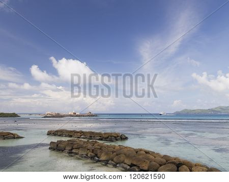 Bright Seascape With A Breakwater Of Rocks