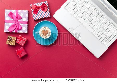 Cup, Gifts And Laptop Lying On The Table