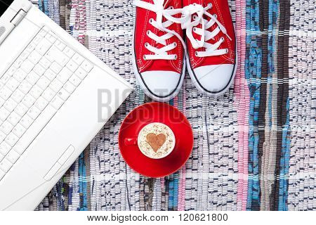 Cup, Gumshoes And Laptop Lying On The Table