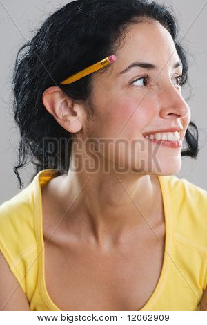 Young woman wearing pencil behind her ear