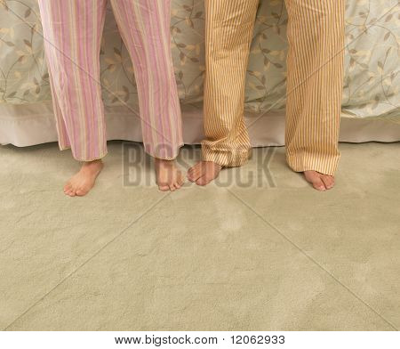 Low section of couple standing in pajamas
