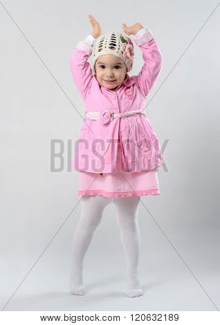 Little Girl Is Standing On Her Tiptoe And Raising Her Hands In The Air, She Is Wearing Pink Cloths A