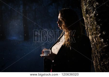 girl drinks tea at night in the forest