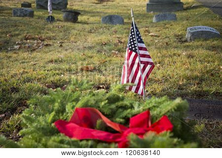 SUCCASUNNA, NJ-DEC 12, 2015: An American Flag in front of wreaths to be laid on veterans graves during the 2015 nationwide Wreaths Across America event.