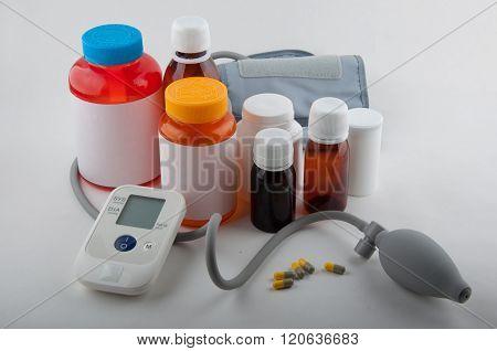Medical Tonometer And Bottles For Pills On White
