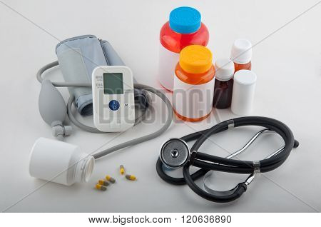 Grey Medical Tonometer, Phonendoscope, Pills And Drug Bottles On White