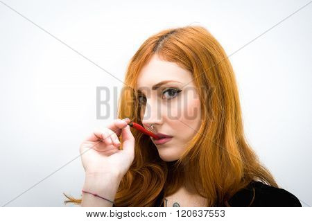 Young Redhead Woman With Red Hot Chili Pepper Portrait