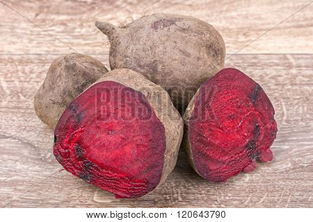 The red beets on a brown wooden background