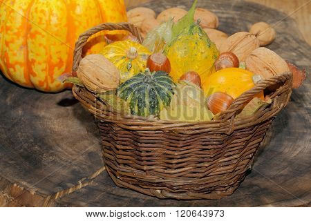 Basket with ornamental gourds autumn leaves various nuts and physalis on a rustic wooden board Thanksgiving decoration