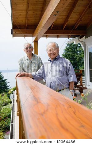 Portrait of two elderly men standing on deck