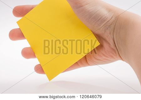 Hand holding yellow color rectangular paper on a white background ** Note: Visible grain at 100%, best at smaller sizes