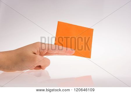 Hand holding orange color rectangular paper on a white background