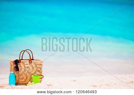 Beach accessories - straw bag, suncream bottle and red sunglasses on the beach
