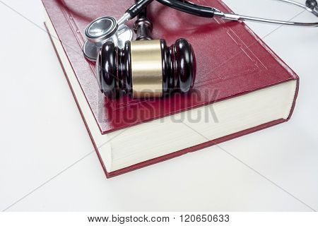 Hammer judge, stethoscope and book on white background