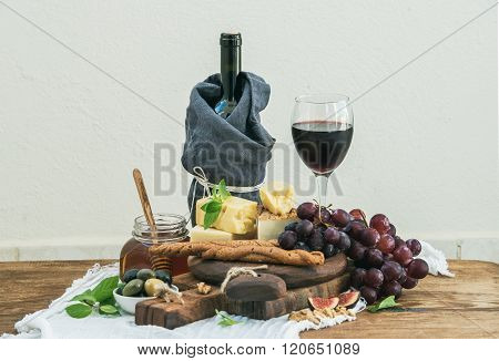 Glass of red wine, cheese board, grapes, fig, strawberries, honey and bread sticks  on rustic wooden