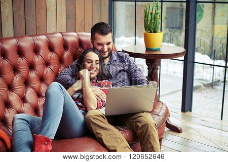 young couple resting on sofa and surfing on internet with laptop at home