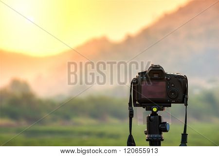 DSLR camera focus on sunrise landscape view.