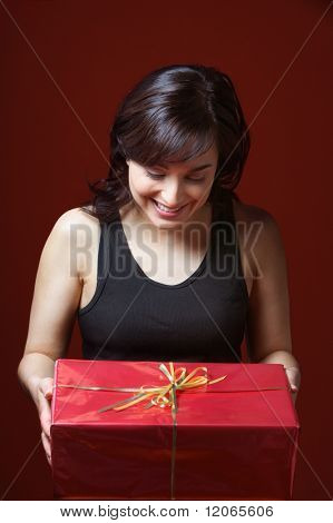 Woman holding gift looking down