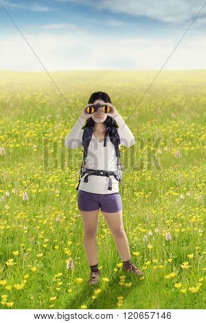 Hiker Using Binoculars On The Meadow
