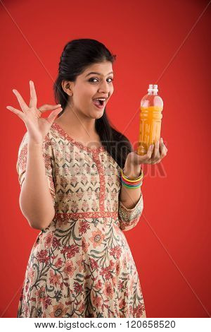 indian pretty girl with orange or mango juice bottle,