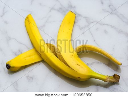 Yellow banana peel over floor marble surface.