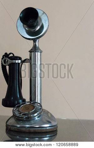 Vintage black telephone with dialing disc in a desk