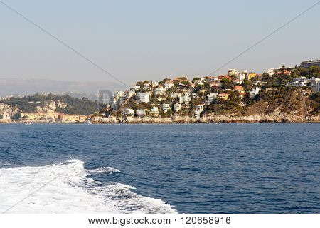 Color DSLR landscape stock image of vacation houses along the French Riviera Mediterranean coastline with blue sea water in foreground. Horizontal with copy space for text ** Note: Visible grain at 100%, best at smaller sizes