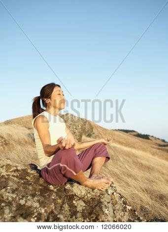Senior woman meditating on a rock outdoors