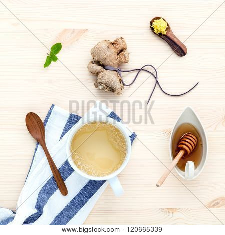 The cup of ginger tea with ginger roots on rustic wooden table.