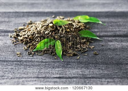 Granulated tea with green leaves on grey background