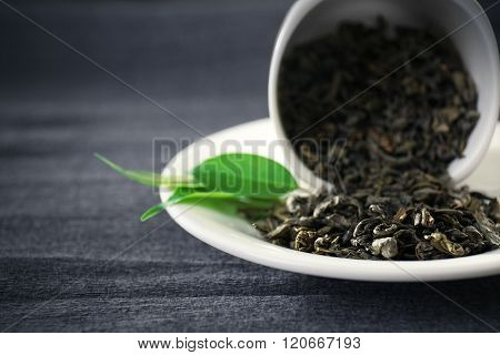 Granulated tea with green leaves in tea-set on grey background