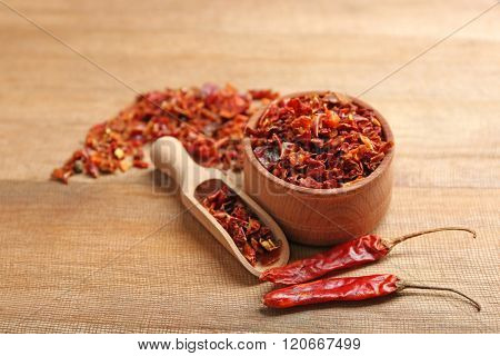 Crusher hot chili pepper on wooden table closeup