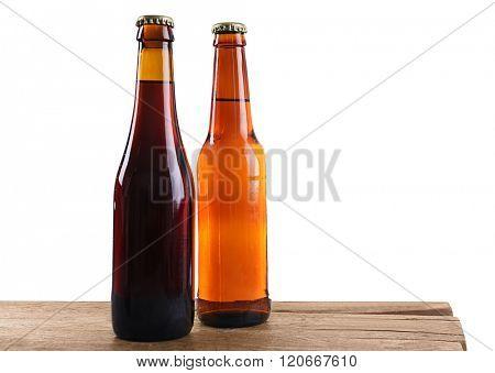 Unlabeled beer bottles on wooden table against white background
