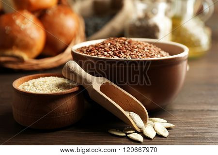 Composition of sesame, flax, pumpkin seeds and buns on wooden table background, closeup